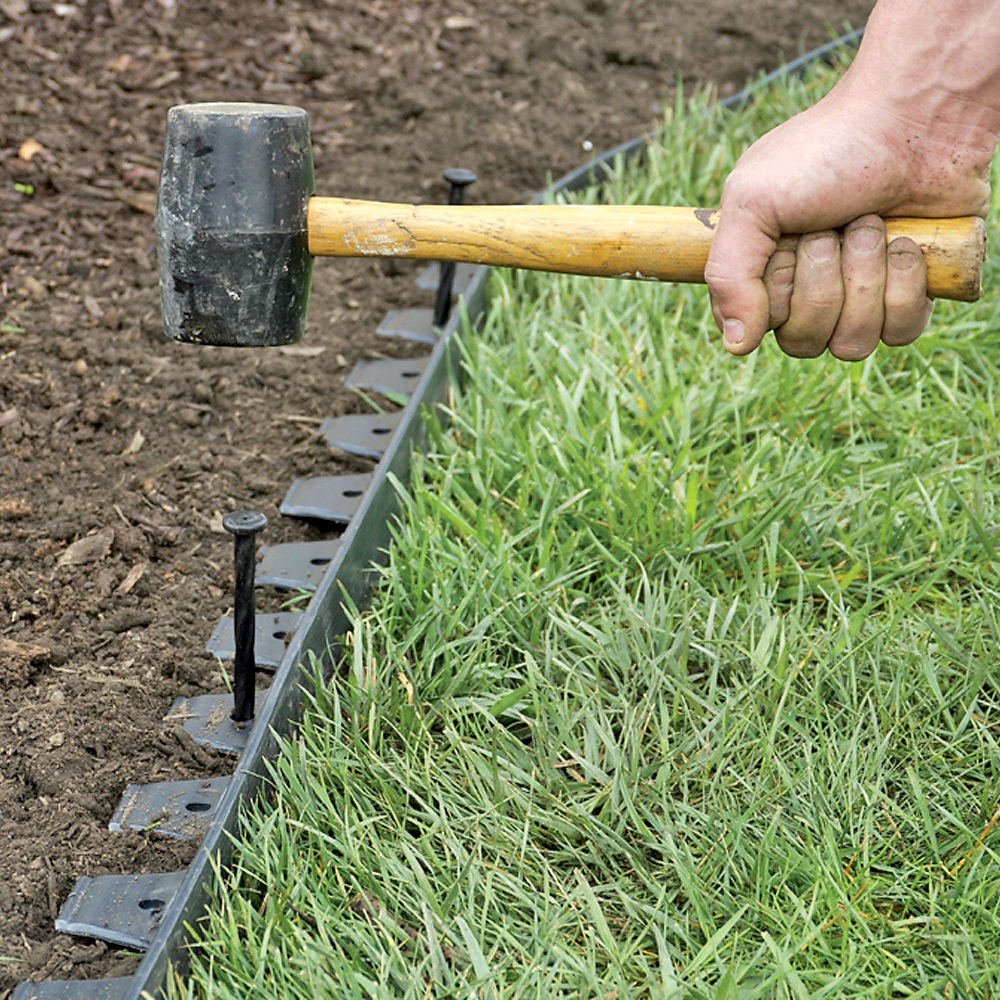 garden edging man using rubber mallet to install edging around garden bed and grass TGWTBIH