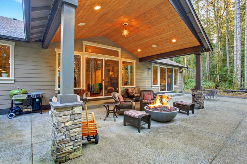 large back yard with grass and covered patio with fire pit XLRHZPZ
