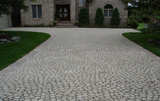 large brick driveway in front of luxury home FYNFVEH
