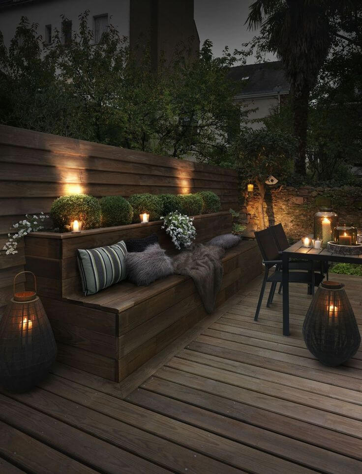 backyard lighting ideas upscale outdoor seating bench lit by candles JXHWUMO