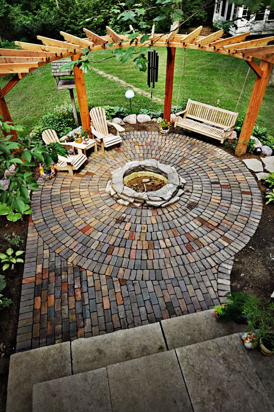 circle-clad brick patio with a fire pit and a swinging day bed XLPMOPP
