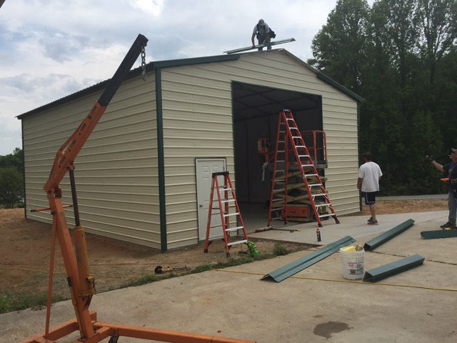 crew building a commercial metal garage, attaching the trim. TAEQWHY