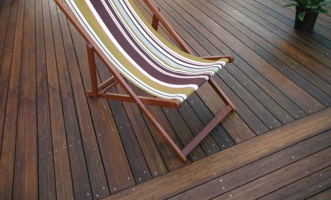 dark stained bamboo decking whith a deckchair YOKVZQP