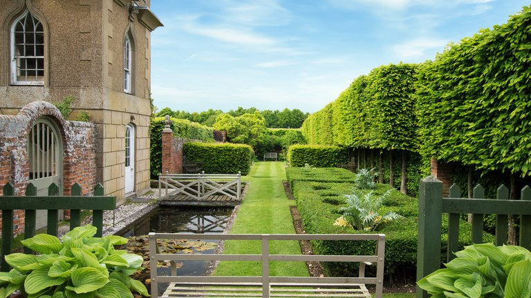garden architecture a long garden with hedgerows opposite a stone building UXRSKPU