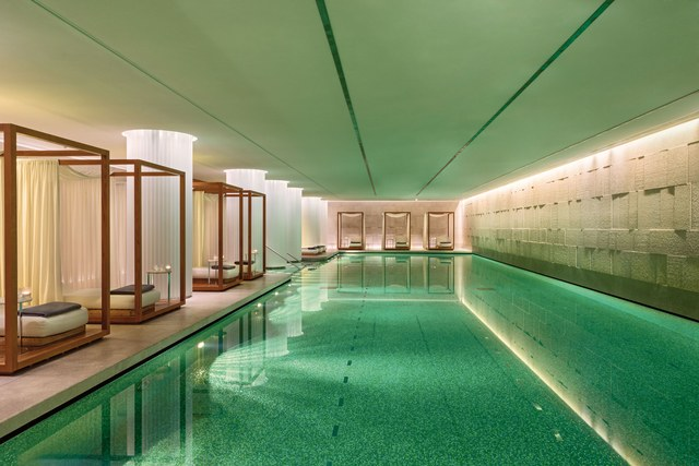 indoor swimming pools indoor pool illuminated water and lounge chairs outside of water MVLUJTI