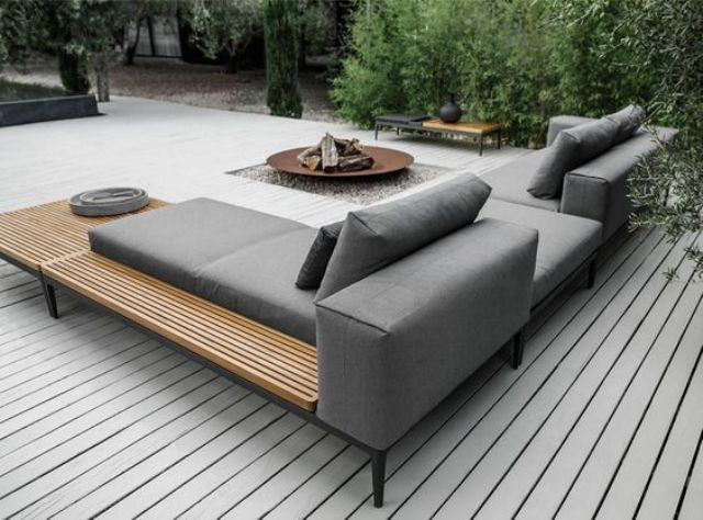 outdoor seating a modern grey upholstered sofa with a wooden shelving for storage PYPIJZB
