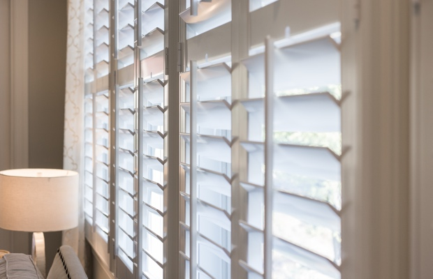 plantation shutters living room with tan walls and white shutters. ZBORRHV