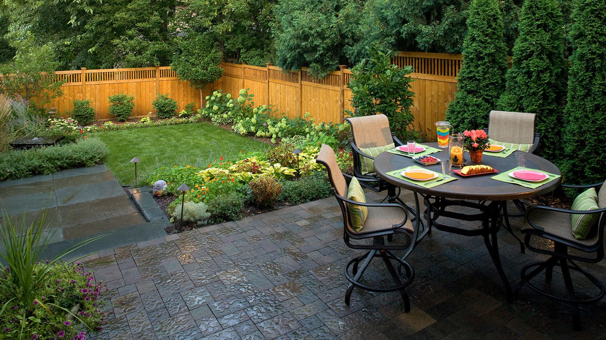 small yard landscaping after: a cedar fence, water feature, dining patio and an edible garden XKSZTOZ
