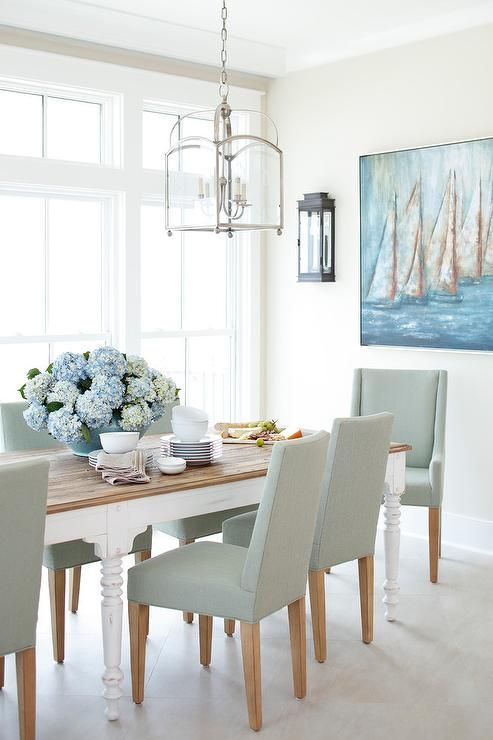 Large dining room windows invite lots of light shining on a white