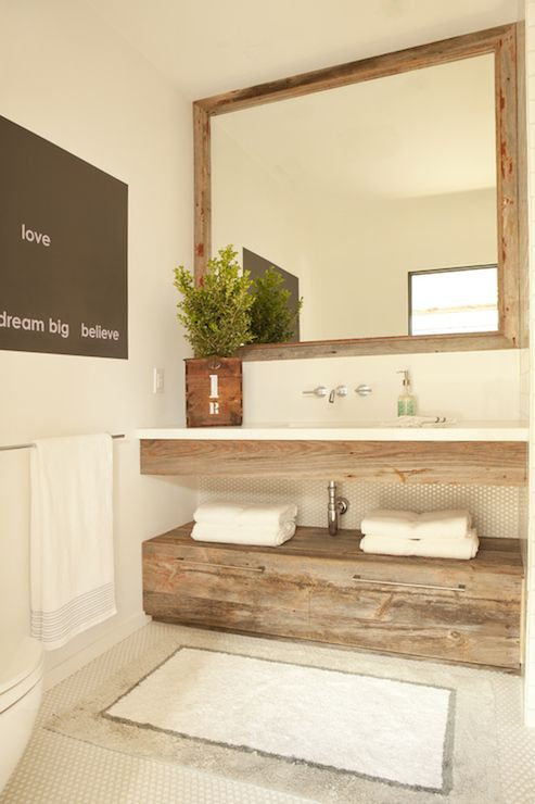 Lovely powder room features reclaimed wood mirror over floating